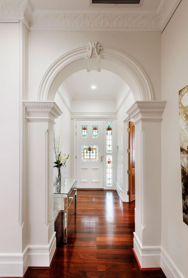 Точечное освещение в белом коридоре с высокими потолками
