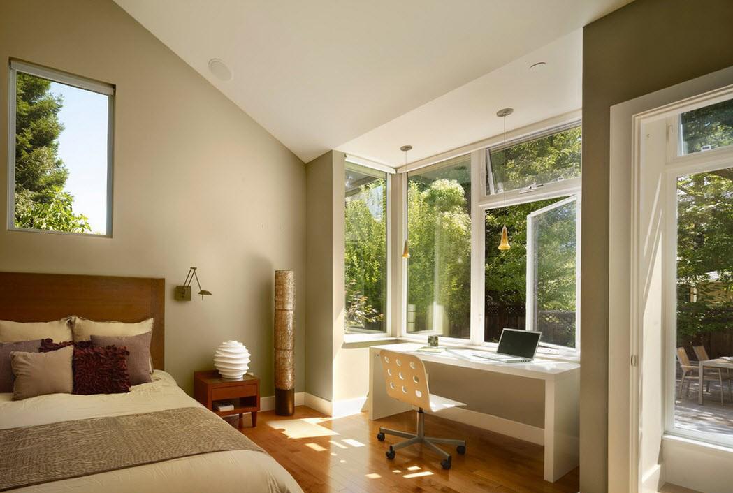 Большое окно дает обилие естественного освещения в спальне с кабинетом