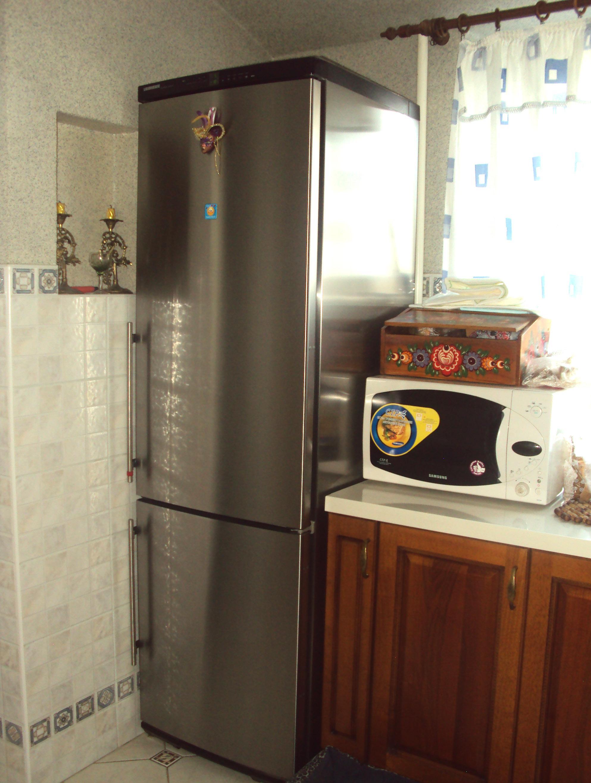 Холодильник в углу небольшой кухни