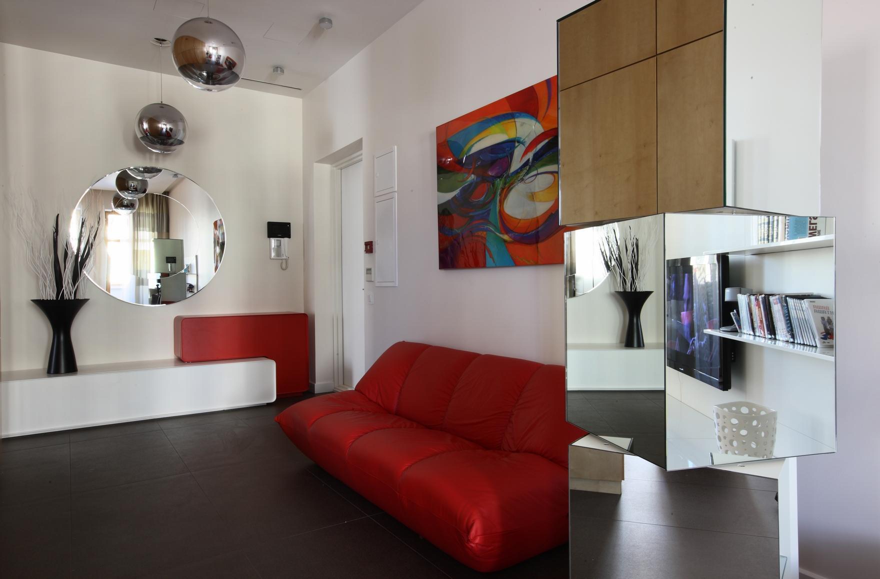Комната для подростка с красным диваном и зеркальными поверхностями