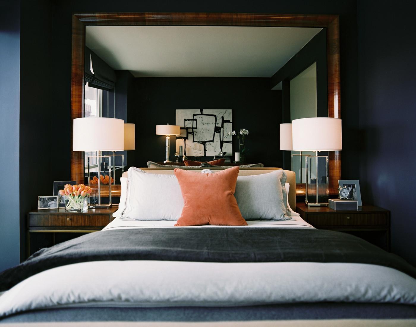 Небольшая спальня с темными стенами и большим зеркалом