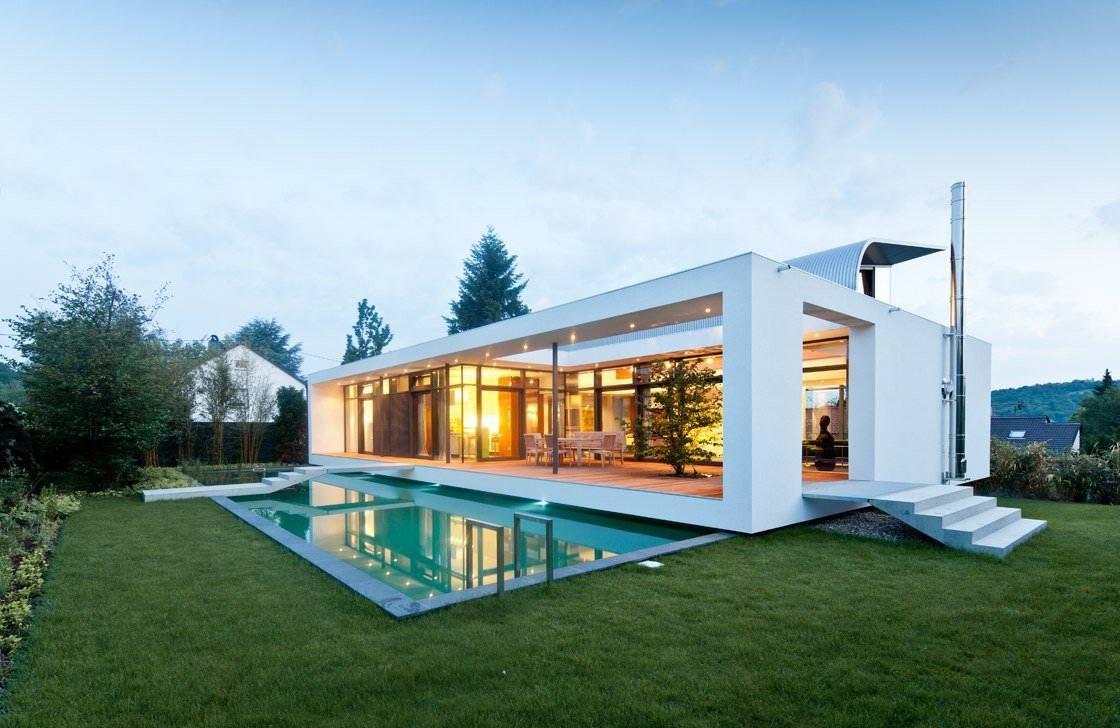 Открытый бассейн на участке у минималистичного дома