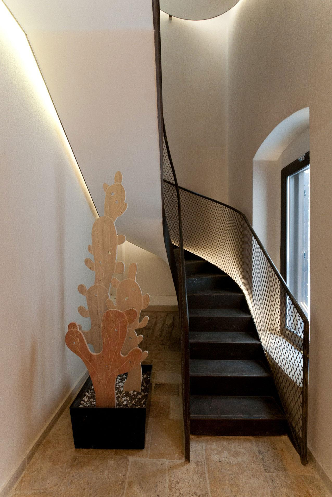 Черная металлическая лестница с перилами из сетки