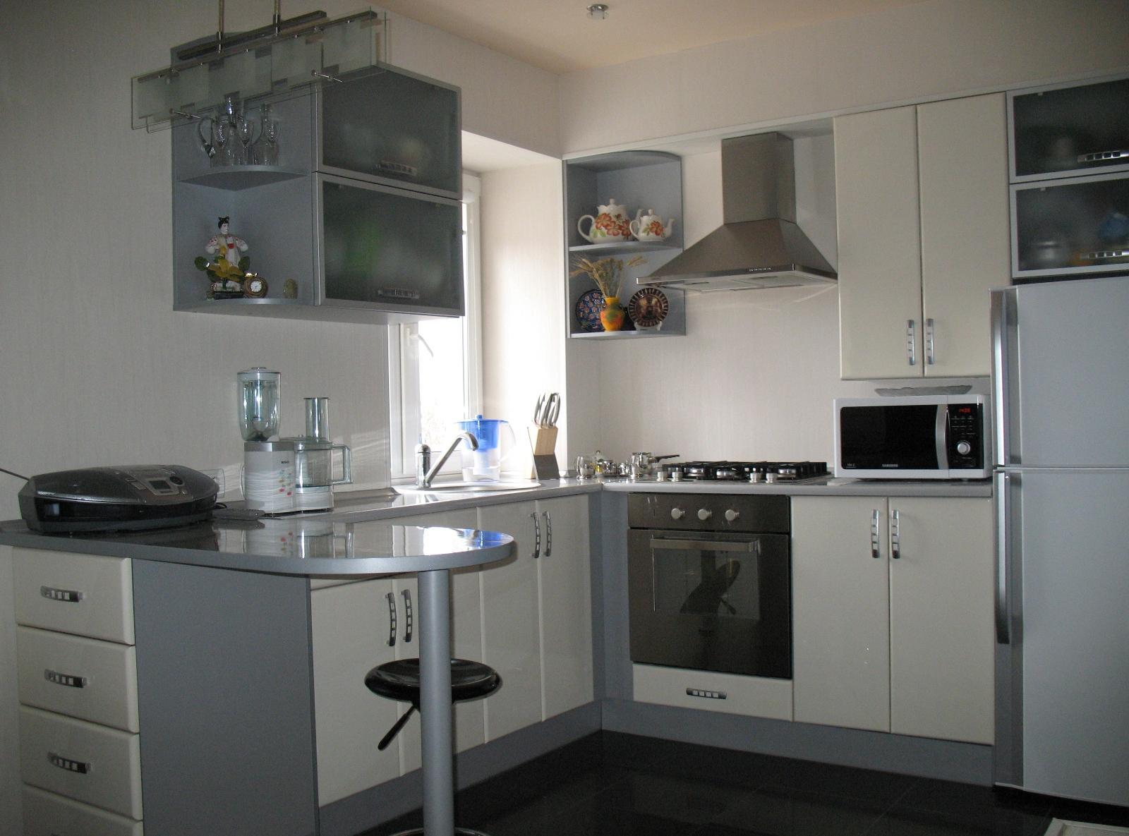 Линейное расположение холодильника на серой кухне