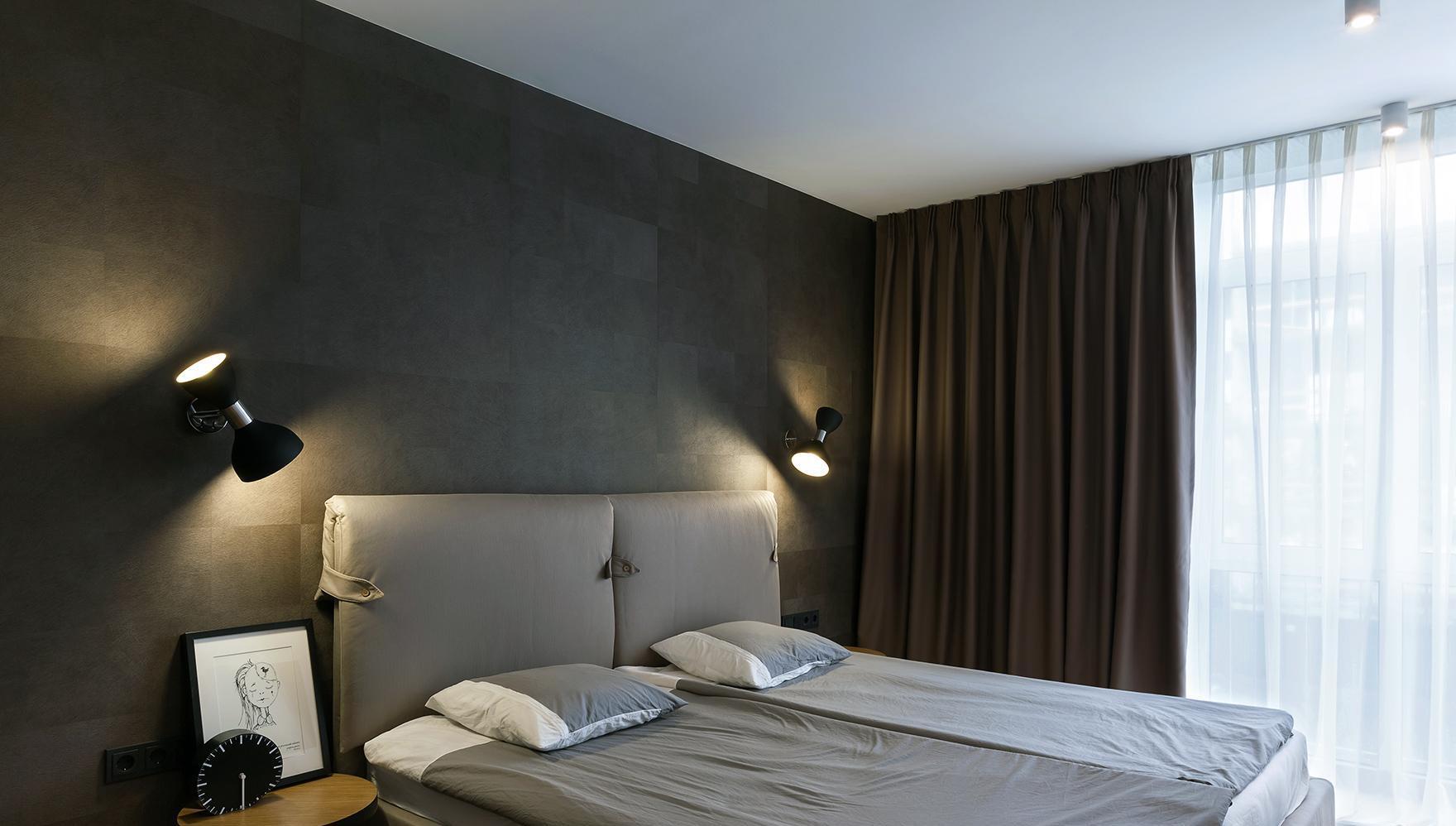 Черная стена в бело-серой спальне