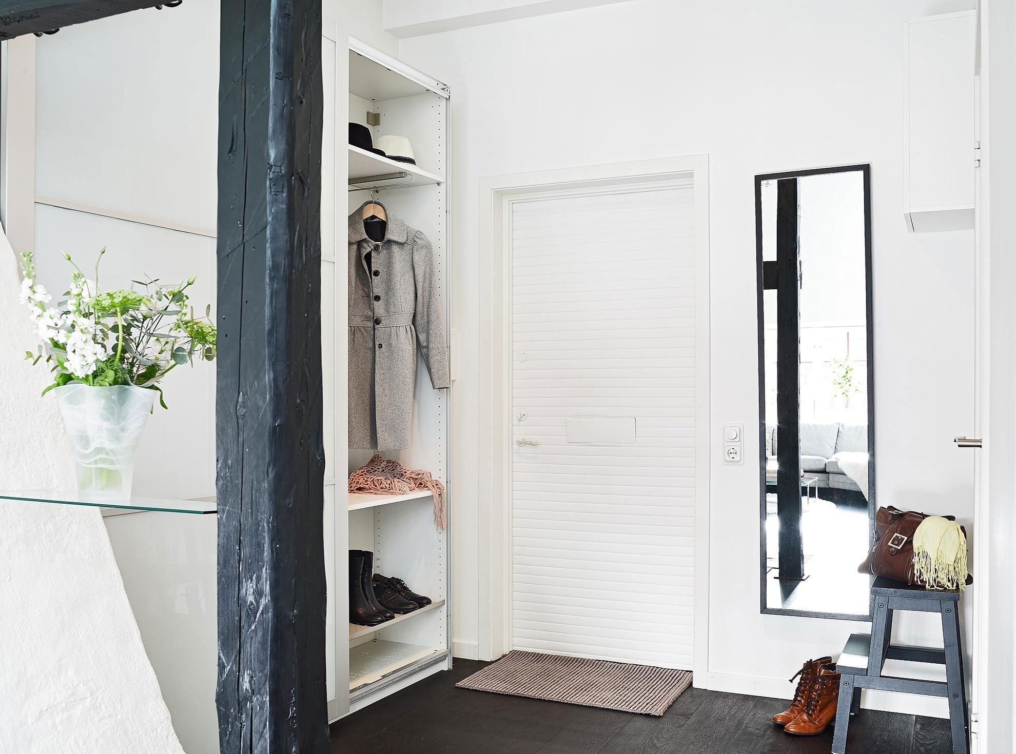 Узкое зеркало в черной раме возле входной двери в прихожей