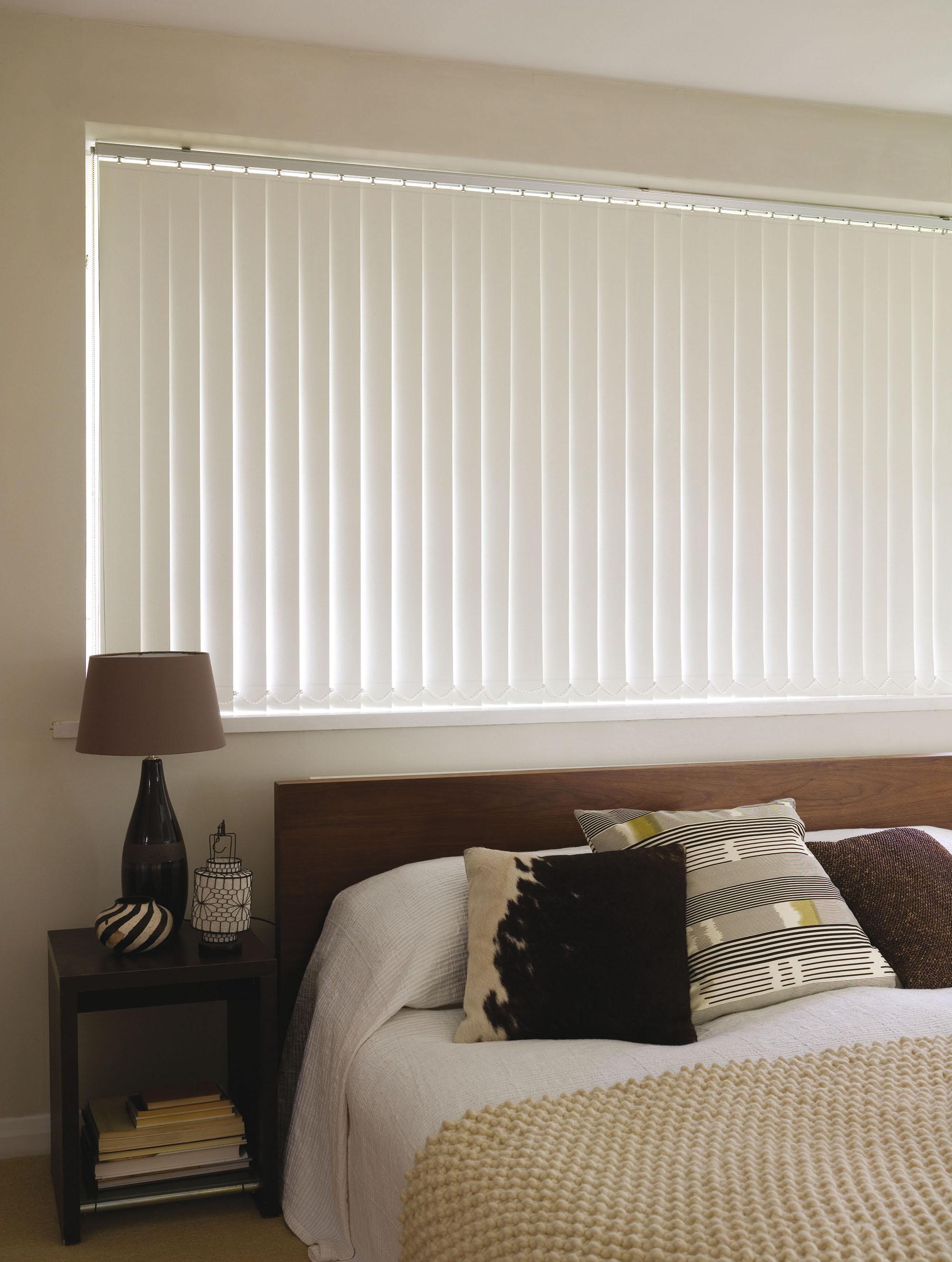 Вертикальные белые жалюзи в спальне