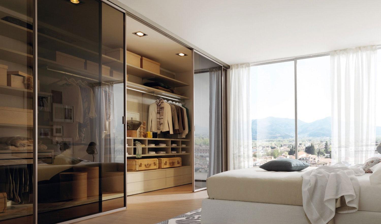 Гардеробная со стеклянными дверями в интерьере спальни