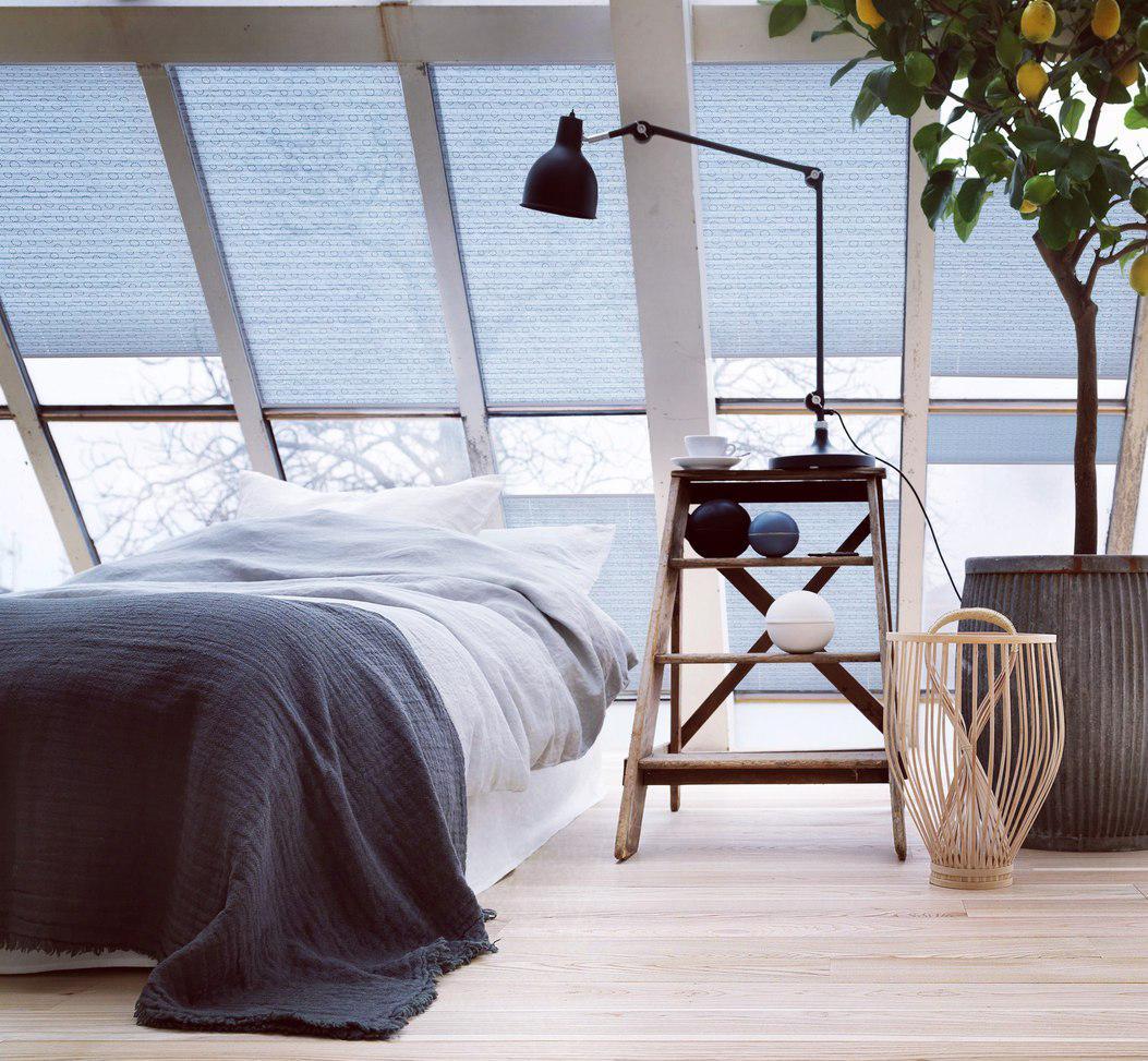 Голубые рулонные шторы в мансардной спальне