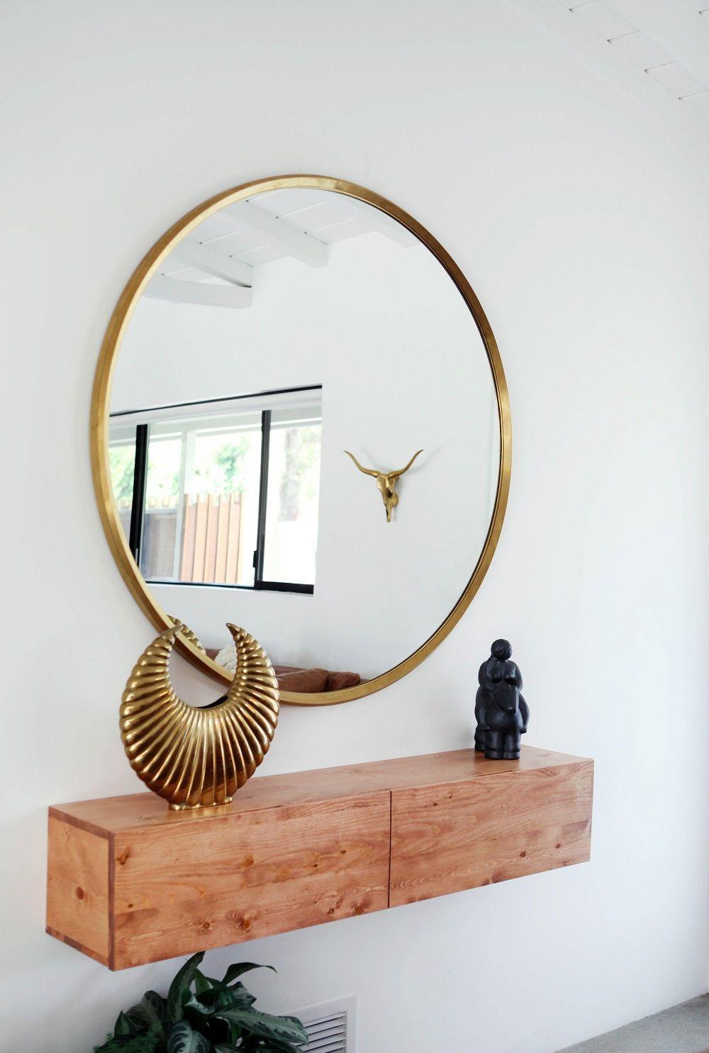 Стильное круглое зеркало в золотистой раме в прихожей