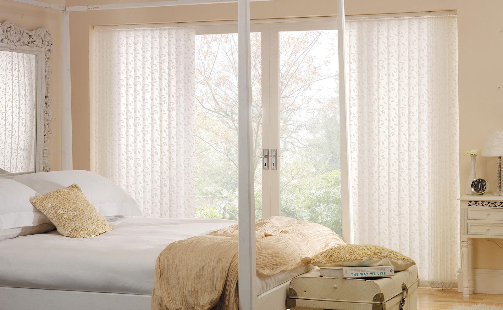 Вертикальные белые с узором жалюзи в спальне
