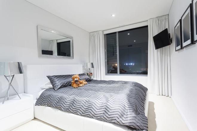 Кровать у окна в квадратной спальне