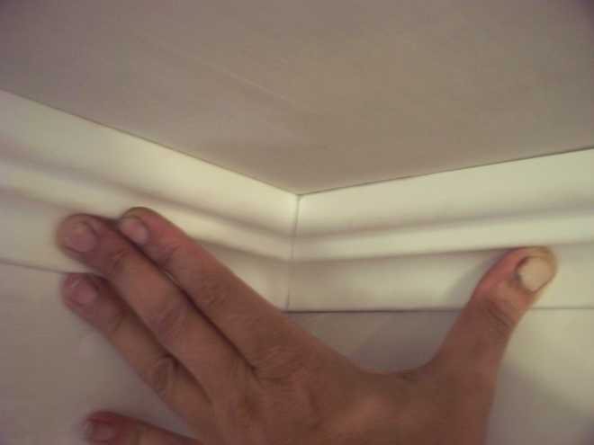 Потолок оклеивают потолочным плинтусом.
